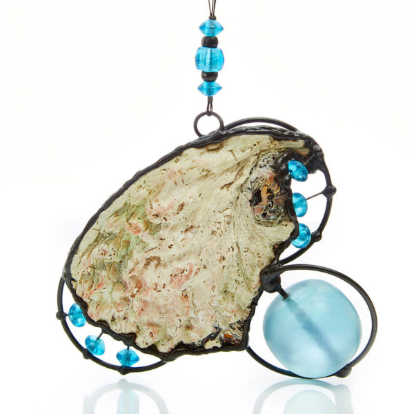 Turquoise glass bead playfully spinning in the circles. Set on the magnificent Perlemoen shell. Connecting us to the Triple Goddess energy.