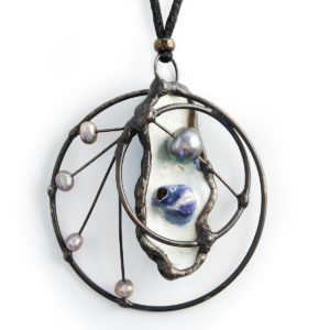 Mother of Pearl shell with Pearls. On this shell a Pearl is emerging. In the circle of life, the Grey Pearls playfully move up & down the connecting lines. Dancing in the joy of life.